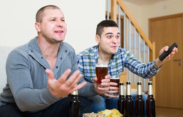 自宅でゲームを観戦している2人の男性スポーツファン