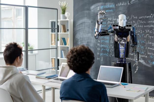 Двое студентов-мужчин смотрят на компьютерного робота автоматизации, стоящего у доски с техническими данными на уроке