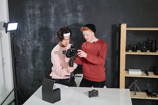Two male vloggers in casualwear looking at digital screen of camera while discussing recorded video in studio