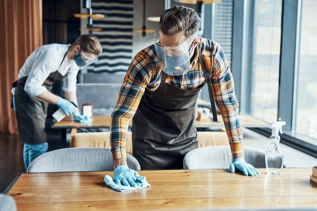 Двое мужчин-официантов в столах для чистки защитной спецодежды в ресторане