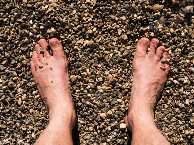 Two male white feet sunbathed on the beach sand