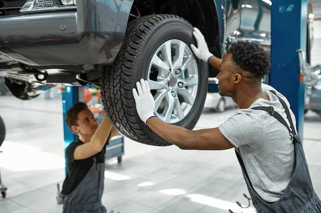 두 명의 남성 근로자가 바퀴, 자동차 서비스를 수정합니다.