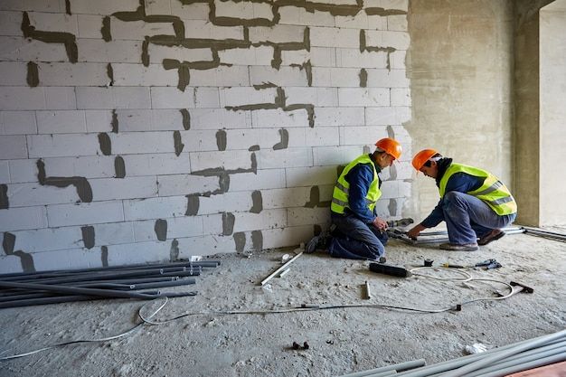 Two males builders in working clothes and safety hard hats are installing plastic pipes using modern tools in a flat of building under construction