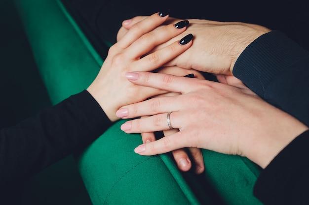 2人の男性と3人の女性がテーブルに手をつないで、ポリアモリーの関係または三角関係を暗示しています。