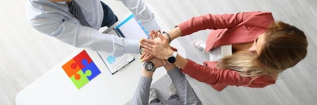 2人の男性と女性は、オフィスの上面図で一方の手のひらをもう一方の手のひらで一緒に保持します。白いテーブルには、ドキュメント、カラフルなパズル、電話があります。
