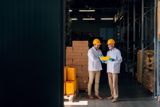 Two man discussing while standing in warehouse. senior holding documents.