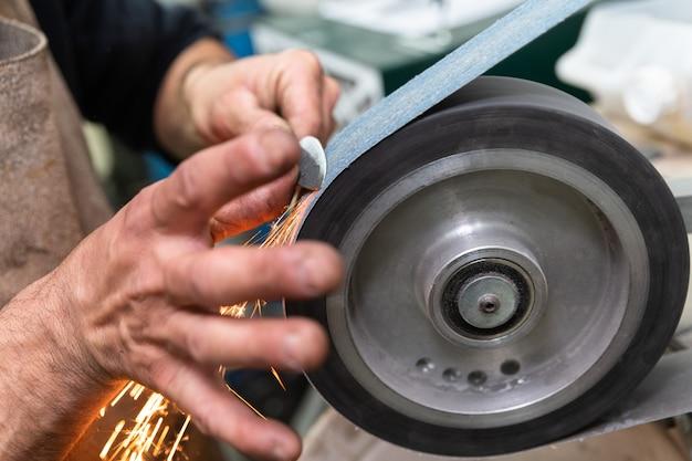 Двое мужчин руками изготавливают стальной нож