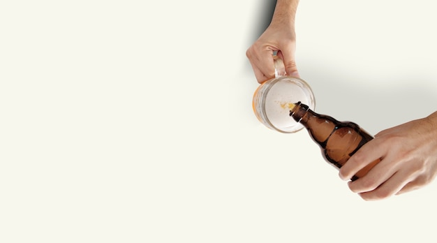 Two man hands with beer mug and bottle on white background