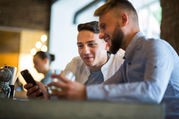 バーに座っている携帯電話を見て二人