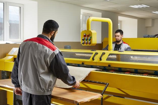 Два человека управляют профессиональным уборочным оборудованием в прачечной, чистят ковер