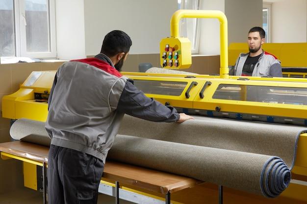 カーペットをクリーニングするランドリーサービスでプロのクリーニング機器を操作する2人の男性