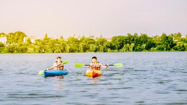 Two man paddling the kayak on lake