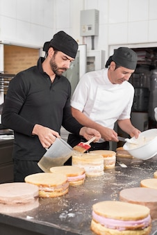Two man pastry chefs working together making cakes at the pastry shop.