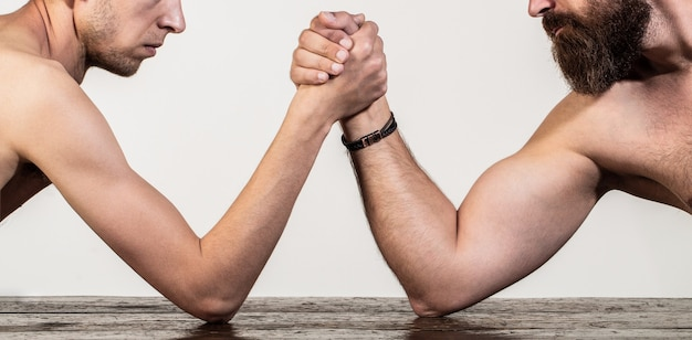 Two man's hands clasped arm wrestling, strong and weak, unequal match. heavily muscled bearded man arm wrestling a puny weak man. arms wrestling thin hand, big strong arm in studio.