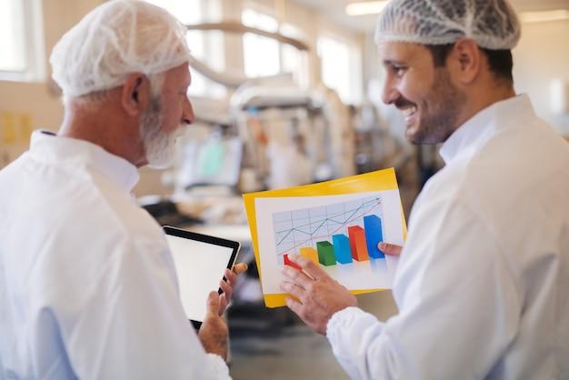 立って話し合っている二人の男。シニアを見ながらタブレットを保持している若い男を示すグラフ。食品工場のインテリア。