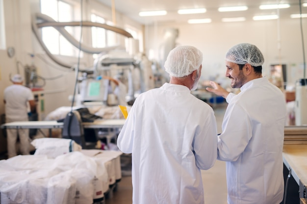 Два человека разговаривают на пищевой фабрике.