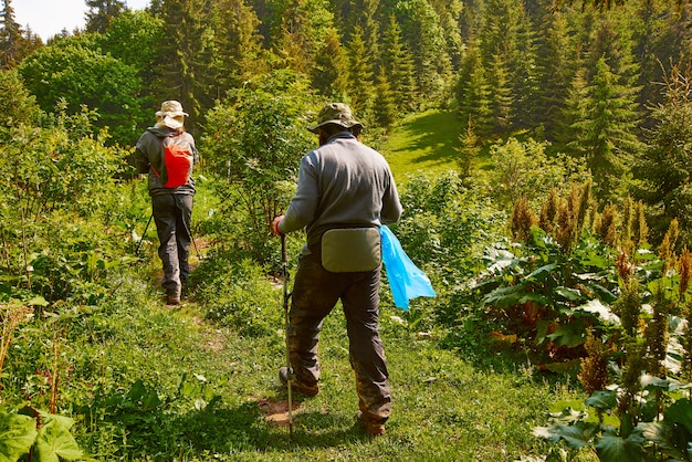 Two man walk through the forest high in the mountains with a garbage bag. protect the nature