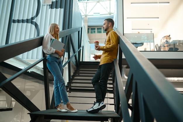 두 명의 관리자가 it 사무실의 계단에서 이야기합니다.