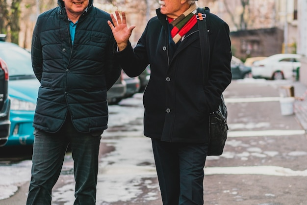 Two mans in black jackets walks and talks on the city's street. male's conversation. adult friends talking. emotional talk. urban. discuss. discussion. gesture. gesturing. leisure