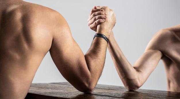 Двое мужчин сцепили руки в рукопашной схватке, сильный и слабый, неравный матч. арм-рестлинг. мускулистый мужчина борется на руках с маленьким слабым мужчиной. оружие борьба тонкая рука