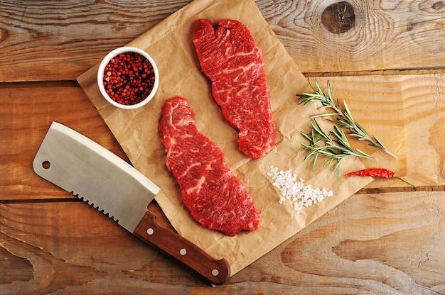 ローズマリー、スパイス、マチェーテナイフで紙に2つの霜降りステーキ