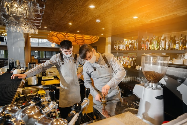 Two masked baristas prepare delicious coffee in the cafe bar