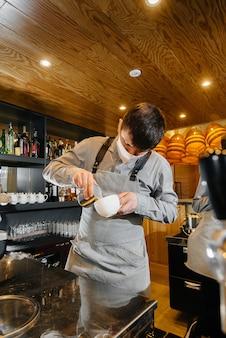 가면을 쓴 두 명의 바리 스타가 카페 바에서 맛있는 커피를 준비합니다. 대유행 기간 동안 레스토랑과 카페의 작업.