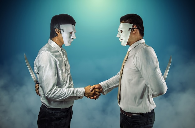 Two masked businessmen shaking hands and holding knifes behind their backs.