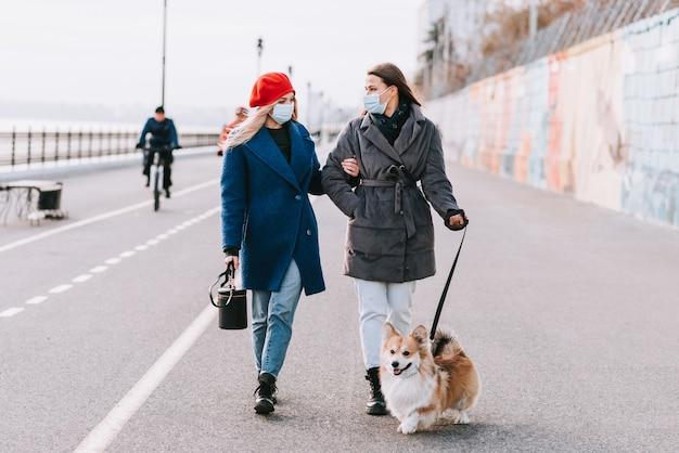 Две молодые женщины в масках вместе выгуливают собаку корги на улице