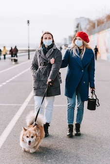 Two masked young women walk a corgi dog together on the street