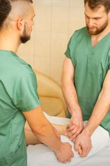 두 명의 안마사가 스파 살롱에서 여성 고객을 위해 네 손으로 발 마사지를 합니다.