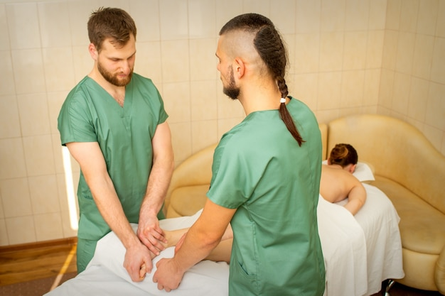 Two masseurs do foot massage in four hands for a female client in a spa salon.