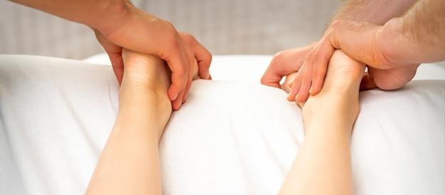 Two masseurs massaging feet of young woman in spa beauty salon