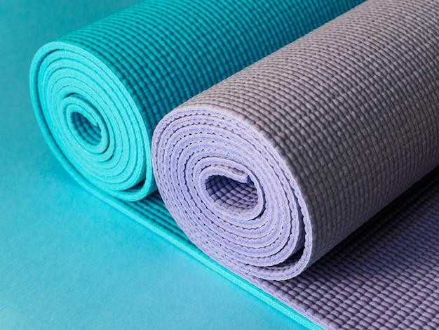 ヨガ、フィットネス、ピラティス用の2つのマット。青と紫のマット。