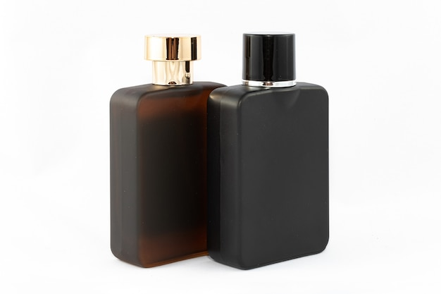Two matte bottles of perfume for men on white background  closeup black and brown blank glass spray ...