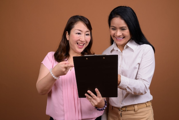 Two mature asian businesswomen together against brown wall