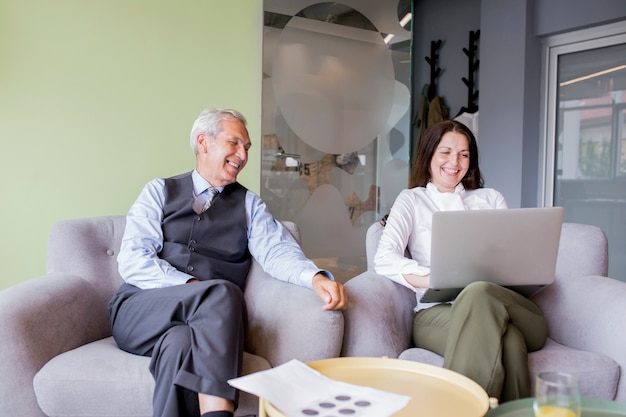 Two mature businessman looking at businesswoman using laptop in the office