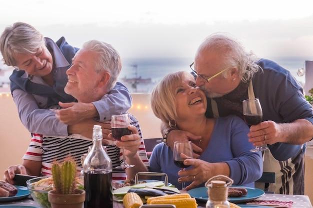 Две зрелые пары остаются вместе с любовными улыбками и поцелуями во время ужина на открытом воздухе на террасе на крыше с океаном и крышами, видят радость и веселятся в ночном досуге и дружбе
