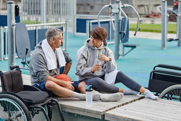 Две зрелые подруги сидят на скамейке, пьют воду и разговаривают друг с другом после спортивной тренировки ...