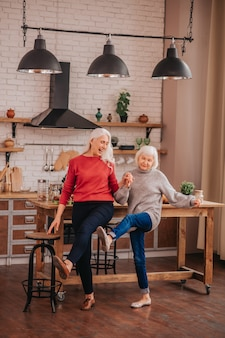 Two mature grey-haired positive ladies dancing in the kitchen