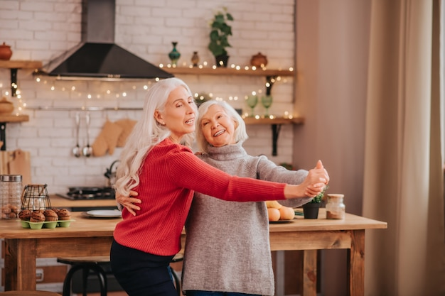Two mature grey-haired positive ladies enjoying their day