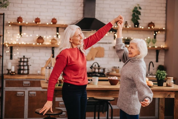 Two mature grey-haired positive ladies having fun