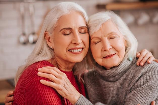 お互いに抱き合っている2人の成熟した白髪のポジティブな女性