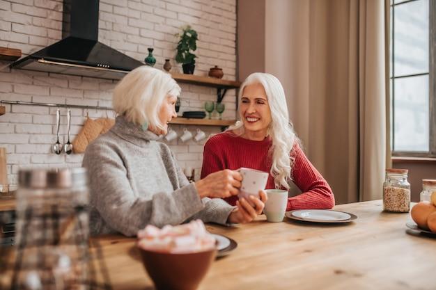 朝食時に話している2人の成熟した白髪のポジティブな女性