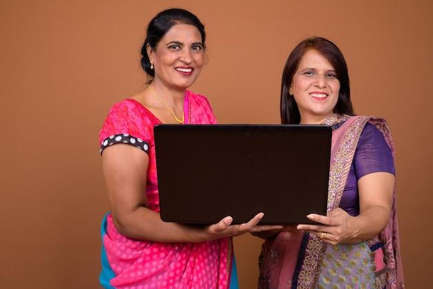 Две зрелые индийские женщины в традиционной индийской одежде сари вместе с ноутбуком