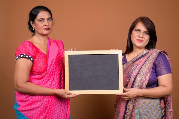 Две зрелые индийские женщины в традиционной индийской одежде сари вместе с шифером