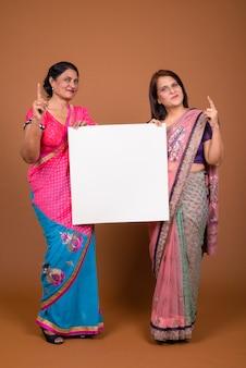 Две зрелые индийские женщины в традиционной индийской одежде сари вместе с белой доской