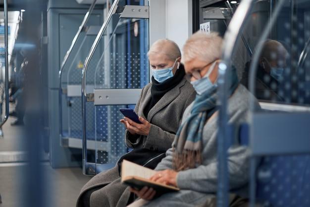 地下鉄車両に座っている保護マスクの2人の成熟した乗客