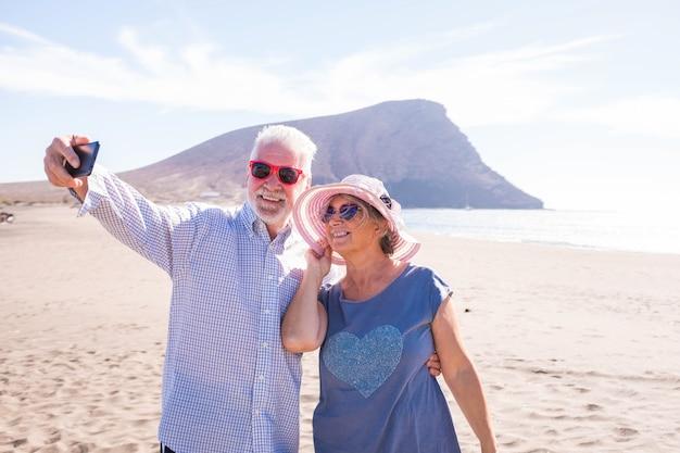 笑顔で楽しんで楽しんでいるビーチで自分撮りをしている2人の成熟した人々-休暇や屋外での休暇を楽しんでいる高齢者や年金受給者-ビーチで晴れた日