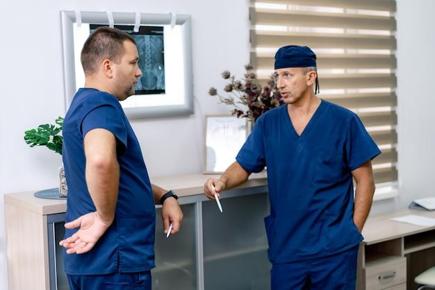 두 명의 성숙한 웃는 의사가 환자 진단에 대해 토론하고 있습니다. 사례를 논의하는 의료진. 병원 홀에서 의사입니다. 확대.